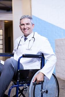 Porträt glücklichen männlichen doktors, der auf rollstuhl im krankenhaus sitzt