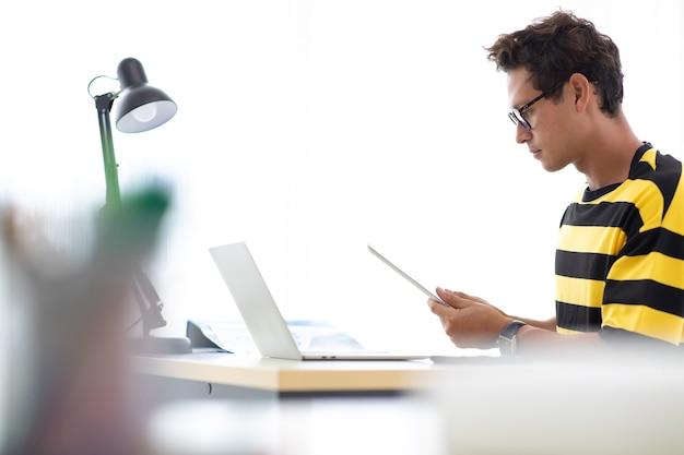 Porträt glücklicher hispanischer kreativer mann, der beschäftigt ist, an laptop-computer im modernen innenministerium zu arbeiten.