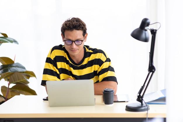 Porträt glücklicher hispanischer kreativer mann, der kaffee trinkt und an laptop-computer im modernen innenministerium arbeitet.