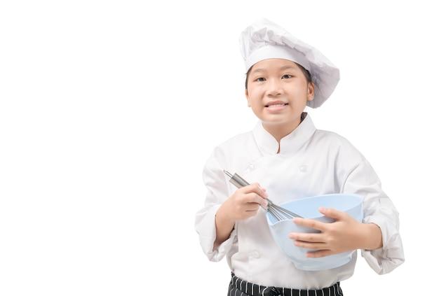 Porträt glücklicher kleiner koch in uniform hält einen schneebesen und eine plastikschüssel, die auf weißer wand und kopierraum isoliert werden