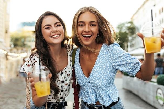 Porträt glücklicher optimistischer aktiver gebräunter freunde, die aufrichtig lächeln und im stadtzentrum spazieren gehen walking