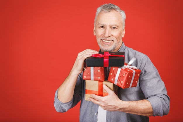 Porträt, glücklicher, super aufgeregter älterer mann, öffnete, packte geschenkboxen aus, isoliert und genoss sein geschenk. positive menschliche emotionen, gesichtsausdruck, gefühlshaltung, reaktion.