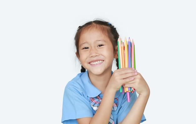 Porträt glückliches kleines mädchen in der schuluniform, die farbstifte hält. bildungs- und schulkonzept.