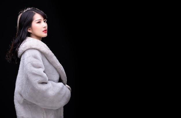 Porträt halber körper von 20 asiatischen frau im grauen pelzkleid-stil der hohen mode über schwarzem hintergrund mit beleuchteter beleuchtung von hinten, kopienraum