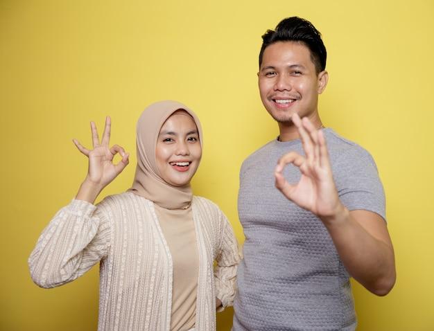 Porträt hijab frau und mann glücklich und zeigen ok zeichen zusammen. isoliert auf gelbem grund