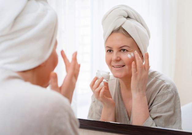 Porträt hübsche ältere frau mit den händen auf ihrem gesichtsspiegel zu hause nach der hautpflege im badezimmer