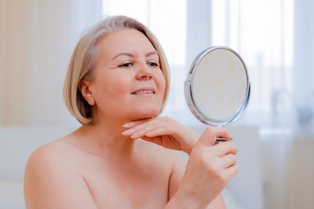 Porträt hübsche ältere frau mit händen auf ihrem gesicht und spiegel