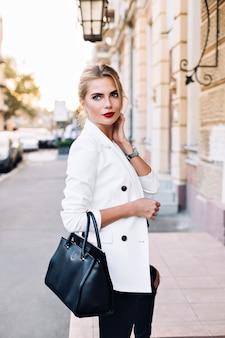 Porträt hübsche frau in der weißen jacke auf der straße in der stadt. sie berührt den hals und schaut zur seite.