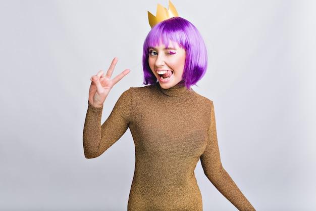 Porträt hübsche frau mit goldkrone, die spaß hat. sie trägt einen violetten haarschnitt, zeigt zunge und sieht glücklich aus