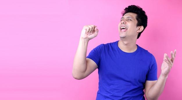 Porträt-hübscher asien-mann, der laut bei der stellung auf rosa hintergrund im studio singt