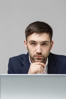 Porträt hübscher stressiger geschäftsmann im anzugschock, der vor laptop am arbeitsbüro schaut.