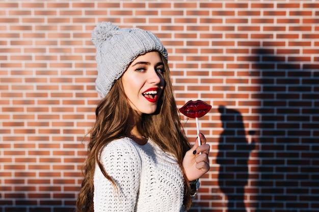 Porträt hübsches brünettes mädchen im weißen pullover und in der strickmütze an der wand draußen. sie hält lutscherrote lippen und lächelt.