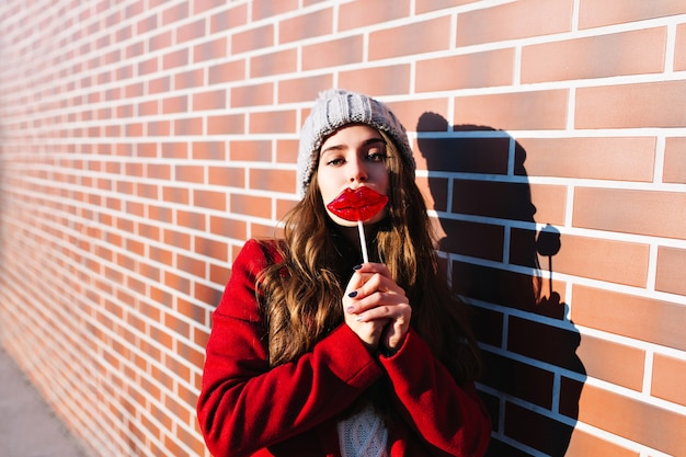 Porträt hübsches brünettes mädchen mit lutscherlippen an der wand draußen. sie trägt eine strickmütze und einen roten mantel.