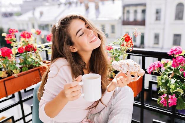 Porträt hübsches junges mädchen mit langen haaren beim frühstück auf dem balkon am morgen. sie hält eine tasse, croissant, hält die augen geschlossen und sieht genossen aus.