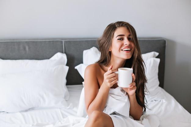 Porträt hübsches mädchen mit frechen schultern, die kaffee auf bett am morgen in der wohnung trinken.