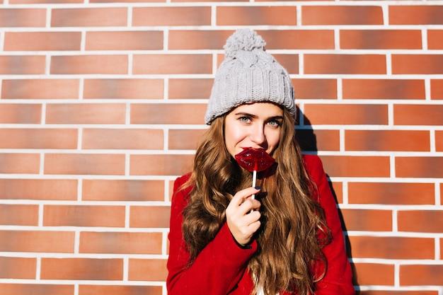 Porträt hübsches mädchen mit langen haaren im roten mantel an der wand draußen. sie trägt eine strickmütze, hält karamelllippen und schaut.