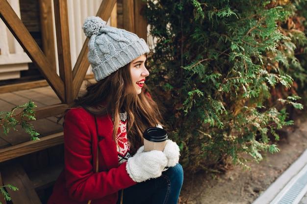 Porträt hübsches mädchen mit langen haaren im roten mantel, der auf holztreppen im freien sitzt. sie hat eine graue strickmütze, weiße handschuhe, hält kaffee und lächelt zur seite.