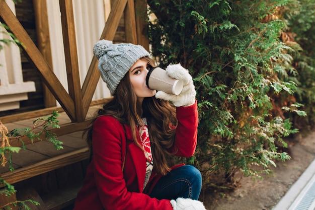 Porträt hübsches mädchen mit langen haaren im roten mantel, strickmütze und weißen handschuhen, die auf holztreppen im freien sitzen. sie trinkt kaffee und schaut.