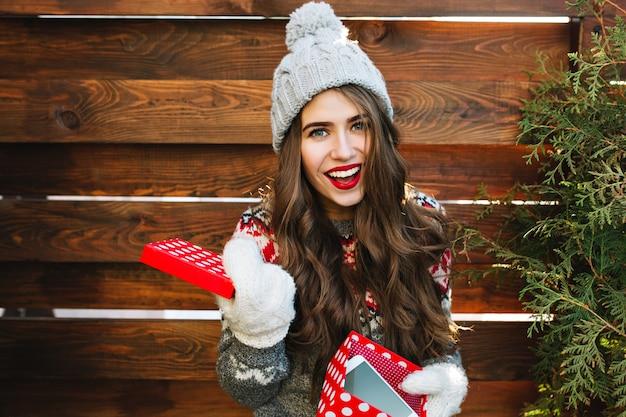 Porträt hübsches mädchen mit langen haaren und roten lippen mit weihnachtsbox auf holz. sie trägt eine strickmütze, handschuhe und lächelt.