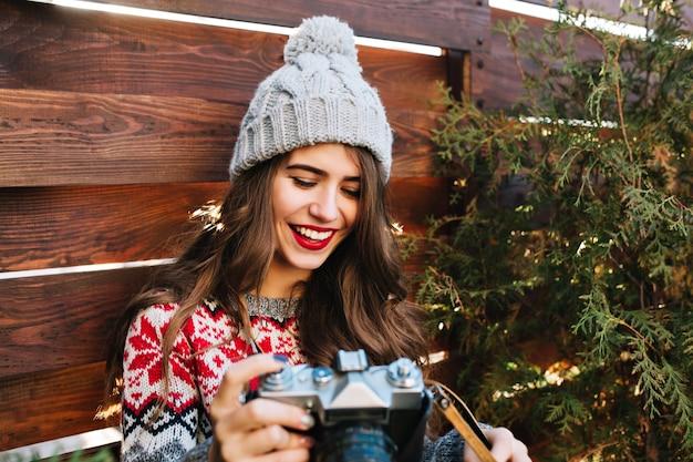 Porträt hübsches mädchen mit schneeweißem lächeln im winterhut, der in den händen auf holz lächelt.