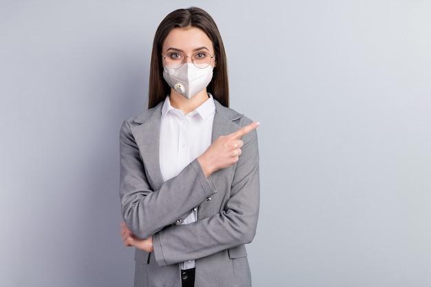 Porträt ihrer attraktiven dame, die die sicherheit n95-maske trägt, die eine kopie des leeren raums leerer platz zeigt, mers cov-krankheit krankheit krankheitstherapie prävention medizin isoliert grauer farbhintergrund