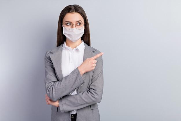 Porträt ihrer attraktiven dame, die eine sicherheitsmaske trägt, die den kopierraum zeigt, dass die influenza-kontamination krankheit krankheit krankheitsprävention jahreszeit grippe grippe isoliert grauer farbhintergrund