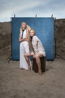 Porträt im freien auf sand vor blauem hintergrund, junge hübsche zwillinge mit langen blonden haaren posiert