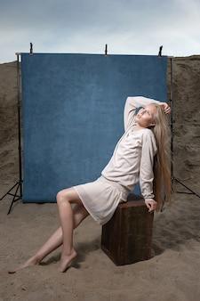 Porträt im freien auf sand vor blauem studiohintergrund, hübsche weibliche aufstellung