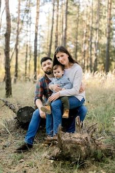 Porträt im freien der glücklichen stilvollen kaukasischen familie in der freizeitkleidung, in den jungen eltern und im niedlichen kleinen kindersohn, auf einem spaziergang im schönen kiefernwald, auf einem baumstamm des alten baumes sitzend und kamera betrachtend