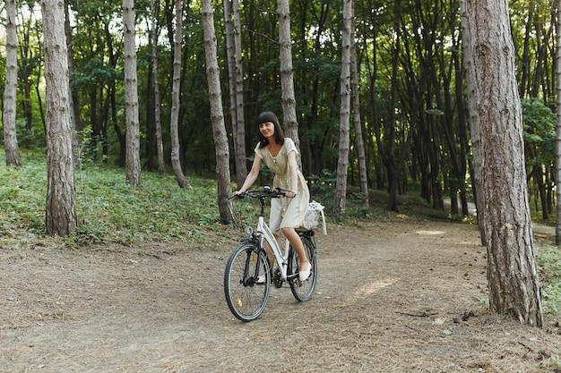 Porträt im freien des attraktiven jungen brunette auf einem fahrrad.