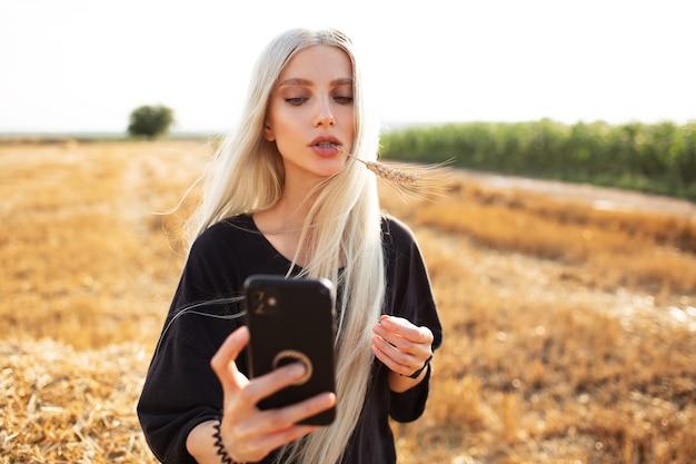 Porträt im freien des jungen netten mädchens mit dem langen blonden haar, das smartphone hält.
