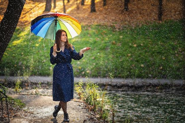 Porträt im freien des jungen schönen glücklichen lächelnden mädchens, das regenschirm hält und unter regen im herbstpark aufwirft