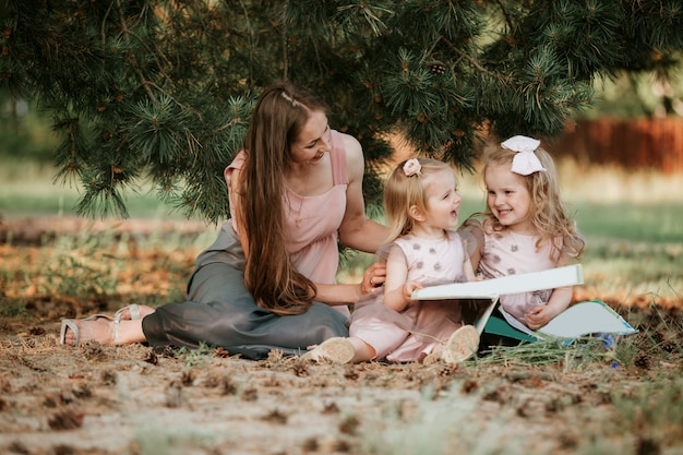 Porträt im freien des kleinen mädchens zwei liest ein buch auf dem gras mit mutter. sie sieht erfreut aus und sie sah sehr entspannt in den armen ihrer mutter aus.