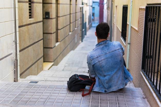 Porträt im freien des modernen jungen mannes mit dem intelligenten telefon, das in der straße sitzt