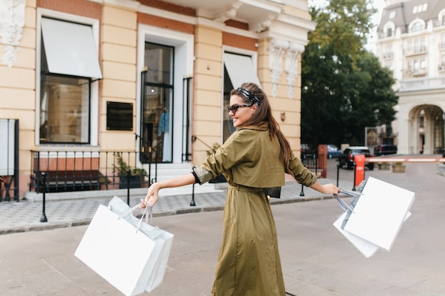 Porträt im freien von der rückseite der fashionista-frau, die herbstwochenende während des einkaufens genießt