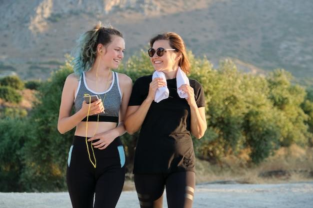 Porträt im freien von mutter und jugendlicher tochter, die sportjogging im freien in den bergen tun. familie, gesunder aktiver lebensstil, kommunikation, menschen