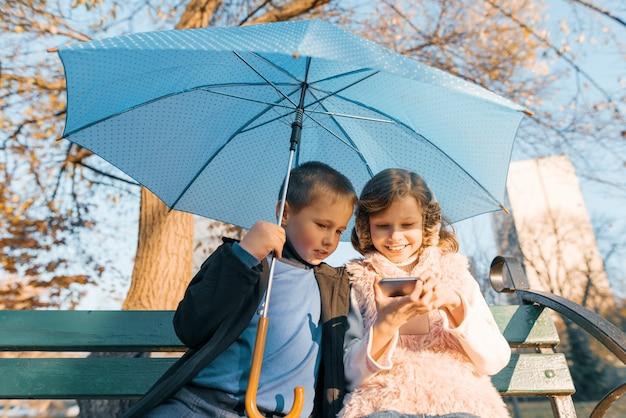 Porträt im freien von zwei lächelnden kindern des jungen und des mädchens, sitzend unter einem regenschirm auf bank im park