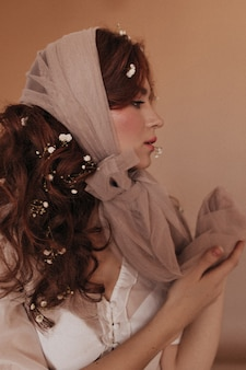 Porträt im profil der lockigen frau mit blumen im dunklen haar, das auf beigem hintergrund aufwirft.