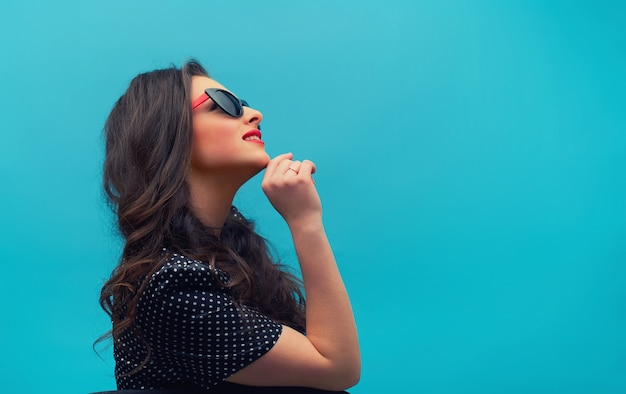 Porträt im profil der schönen jungen frau auf dem schwarzen weinlese-tupfenkleid an der blauen wand. junges weibliches modell.