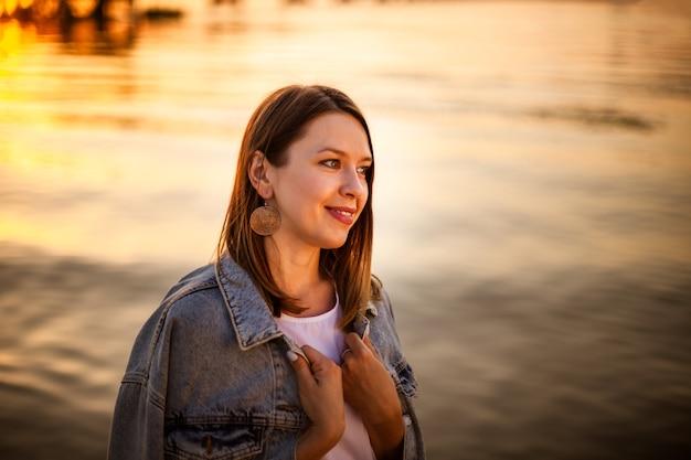 Porträt im profil einer glücklichen frau bei einem leuchtend orangefarbenen herbstsonnenuntergang am strand am meer
