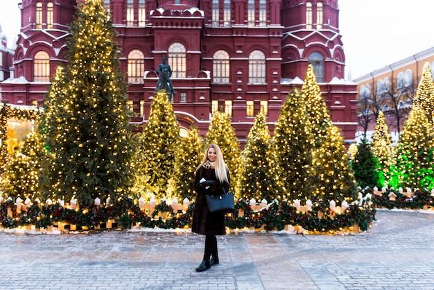 Porträt in vollem wachstum, russische schöne frau in einem nerzmantel auf dem roten platz in moskau in der weihnachtszeit