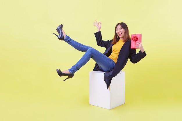 Porträt in voller länge attraktive junge frau, die geschenk schwebt, isolierten gelben hintergrund