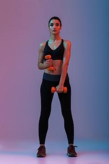 Porträt in voller länge der athletischen frau in sportbekleidung, die übungen mit hanteln macht, lokalisiert über lila wand