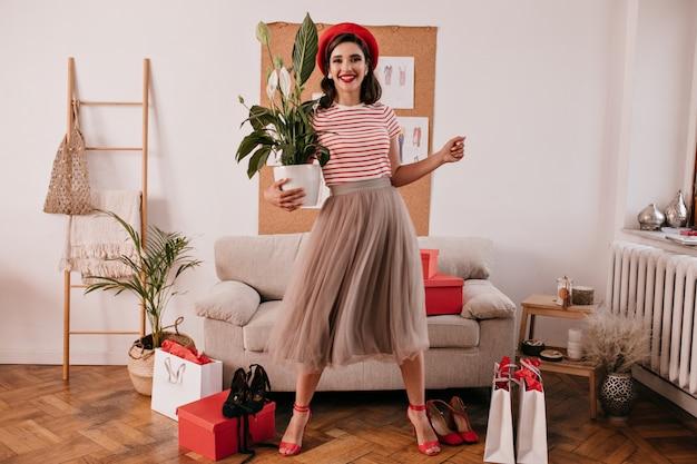 Porträt in voller länge der dame im kleid, das mit pflanze aufwirft. junge moderne frau in stilvollen kleidern schaut auf kamera und lächelt.