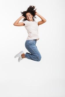 Porträt in voller länge der entzückenden amerikanischen frau mit afro-frisur, die jeans und t-shirt tragend springt und sich mit perfektem lächeln freut, lokalisiert über weißer wand