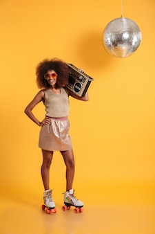 Porträt in voller länge der fröhlichen afrikanischen disco-frau mit hand auf ihrer taille, die in retro-kleidung steht, die auf rollschuhen steht und boombox hält