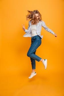 Porträt in voller länge der fröhlichen frau, die jeans und turnschuhe trägt, die mit siegesgeste springen oder laufen, lokalisiert über gelbem hintergrund