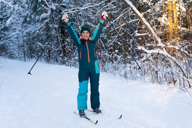 Porträt in voller länge der jungen aktiven schönen frau, die im verschneiten winterwald ski fährt