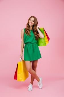 Porträt in voller länge der jungen schönen gelockten frau des lesekopfes im grünen kleid, das bunte einkaufstaschen hält