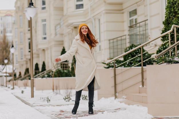 Porträt in voller länge der modischen ingwerfrau, die im kalten dezembertag lächelt. frohes kaukasisches mädchen, das winter genießt.